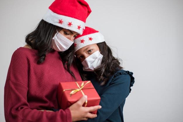 Moeder en dochter knuffelen samen met droevige ogen met kerstmis tijdens de covid-pandemie.