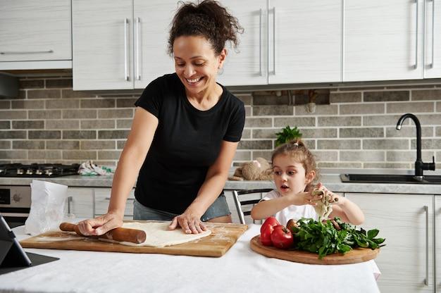 Moeder en dochter koken samen pizza, rollen het deeg uit met een houten deegroller en hebben samen lol in de keuken