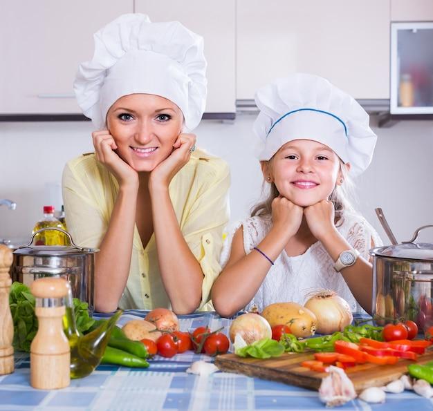 Moeder en dochter koken vegeterian gerecht binnenshuis