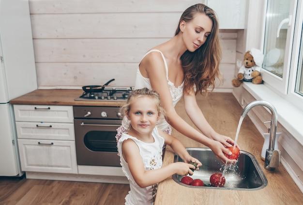 Moeder en dochter kokende en wassende groenten in keuken