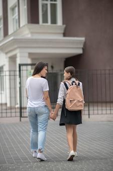 Moeder en dochter komen naar schoolpoort samen hand in hand gelukkig communiceren