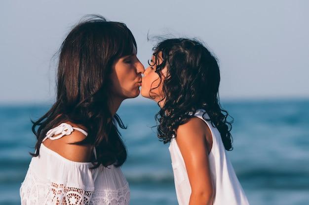 Moeder en dochter kussen elkaar op het strand