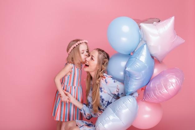 Moeder en dochter kussen en brengen tijd door met ballonnen op een roze ondergrond. familie
