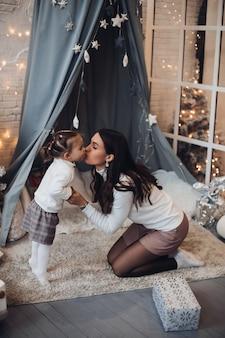 Moeder en dochter kussen met kerstmis onder sneeuw.
