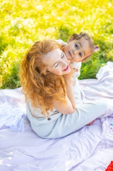 Moeder en dochter lachen en knuffelen zittend op een deken in het park het concept van een gelukkig gezin...