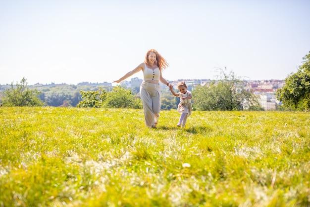 Moeder en dochter lachen en plezier hebben in het park het concept van een gelukkige familie vriendschap en liefde