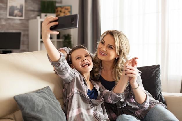 Moeder en dochter lachen terwijl ze een selfie maken op de bank in de woonkamer.