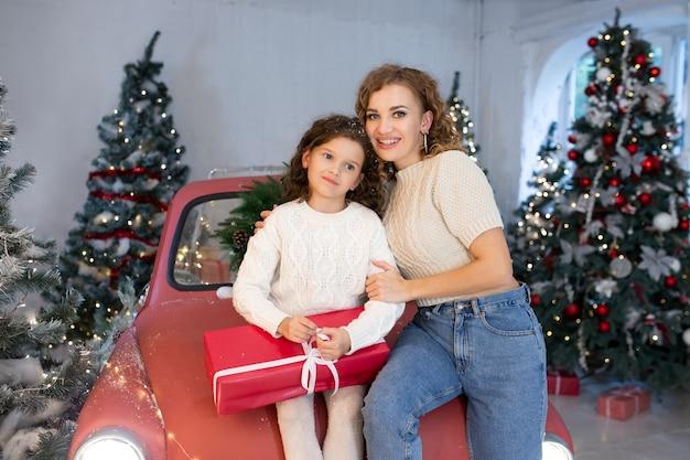 Moeder en dochter lachend met geschenkdoos in de buurt van de kerstboom binnenshuis.