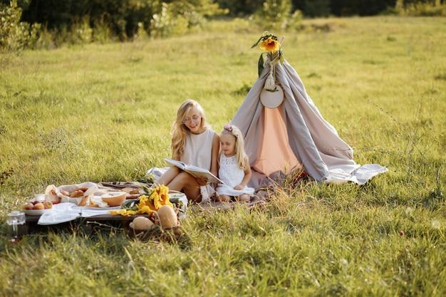 Moeder en dochter lazen in de zomer een boek op een picknick. zij zijn blij