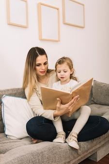 Moeder en dochter leesboek in de woonkamer