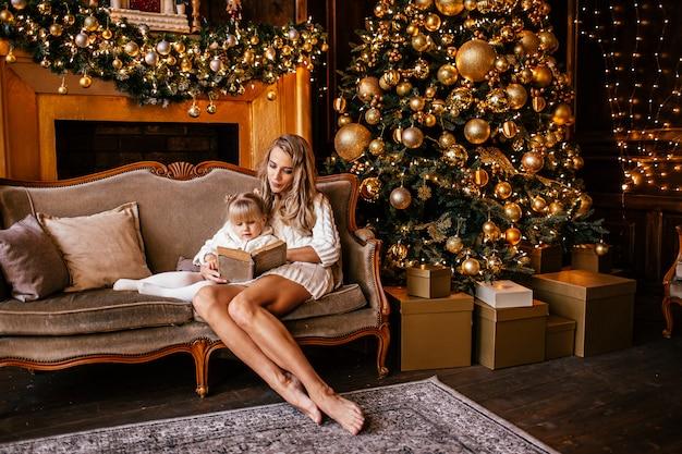 Moeder en dochter lezen van een boek bij open haard op kerstavond. ingerichte woonkamer met boom, open haard en geschenken. winteravond thuis voor ouders en kinderen.