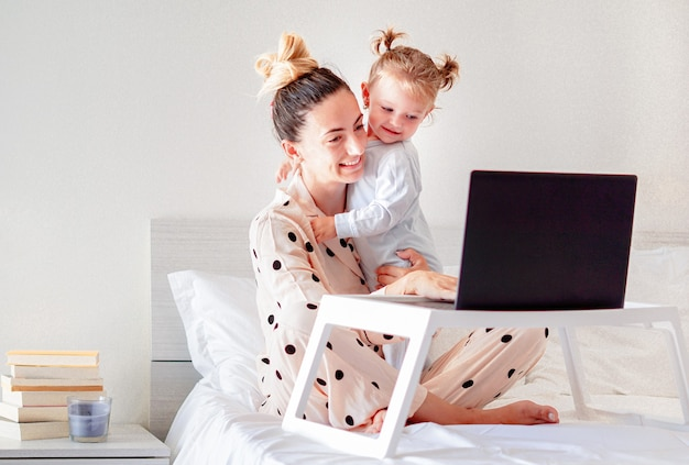 Moeder en dochter liggen in bed met pyjama aan en glimlachen naar elkaar - jonge moeder werkt vanuit huis in de slaapkamer met haar laptop op ontbijttafel en boeken opzij