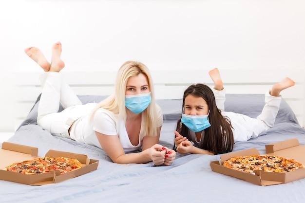 Moeder en dochter liggen thuis in bed met pizza tijdens quarantaine, quarantaine-vrije tijd