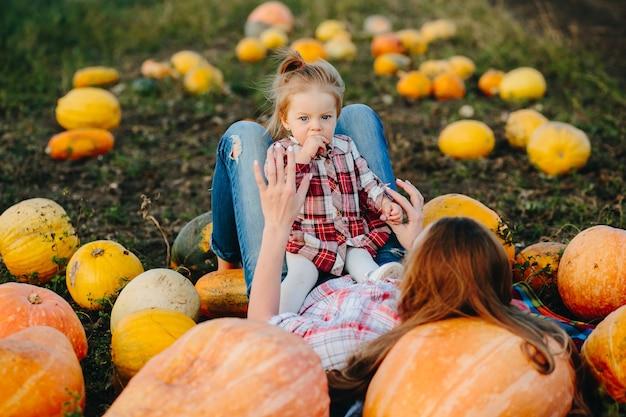 Moeder en dochter liggen tussen pompoenen op het veld