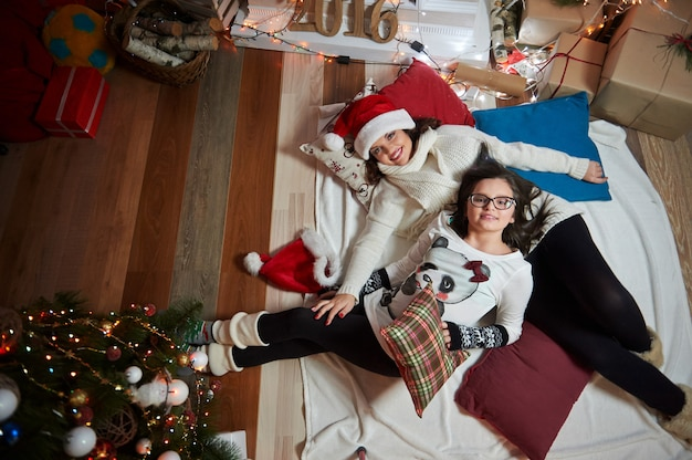 Moeder en dochter liggend op de vloer samen thuis op kerstmis