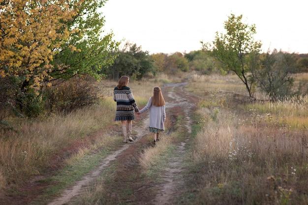 Moeder en dochter lopen in de weide