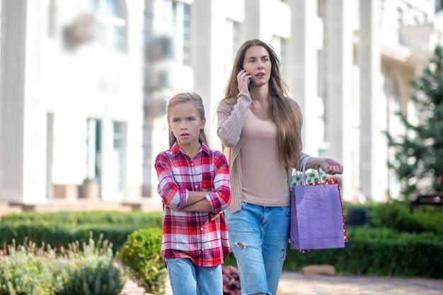 Moeder en dochter lopen langs de straat met boodschappentassen