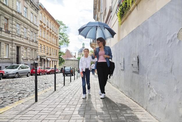Moeder en dochter lopen onder een paraplu langs straat