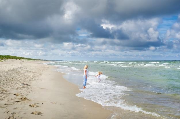 Moeder en dochter lopen samen langs de oevers van de baltische zee in litouwen.