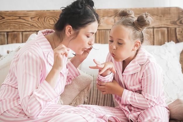 Moeder en dochter make-up samen. kleine dingen van het meisje. vrouwelijke vrijetijdsbesteding.