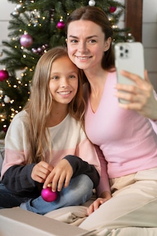 Moeder en dochter maken een selfie naast de kerstboom