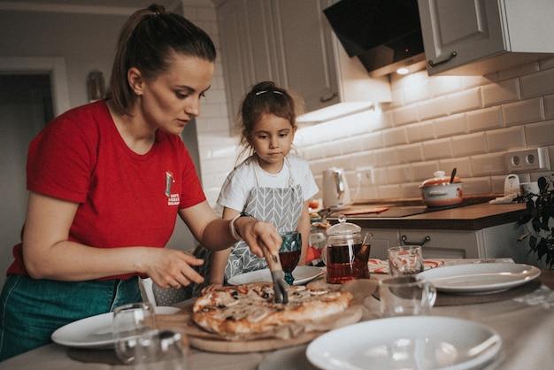 Moeder en dochter maken pizzafamilie