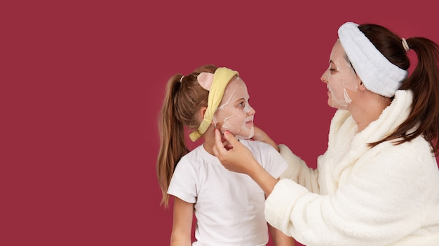 Moeder en dochter maken stoffen gezichtsmasker, familie huidverzorging op geïsoleerd rood