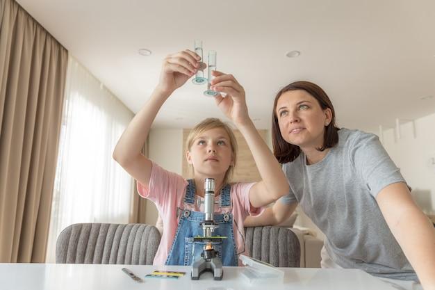 Moeder en dochter maken thuis chemische experimenten met microscopen