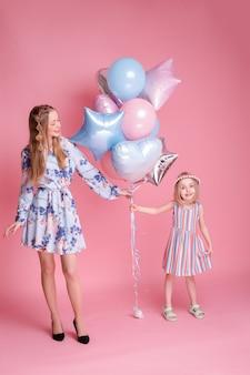 Moeder en dochter met ballonnen gelukkig op roze oppervlak