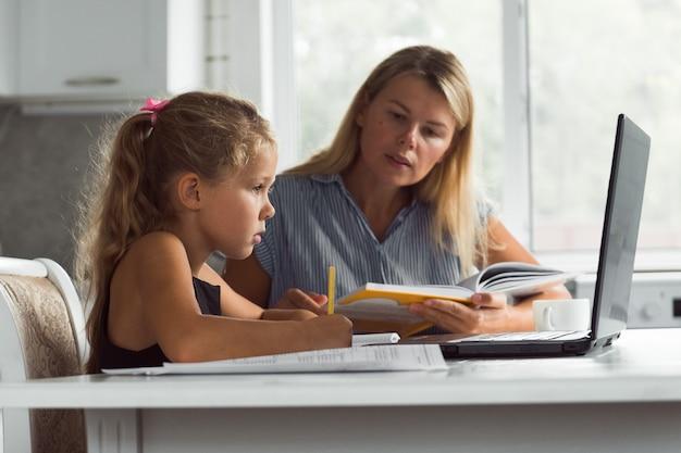Moeder en dochter met behulp van laptop online leerconcept
