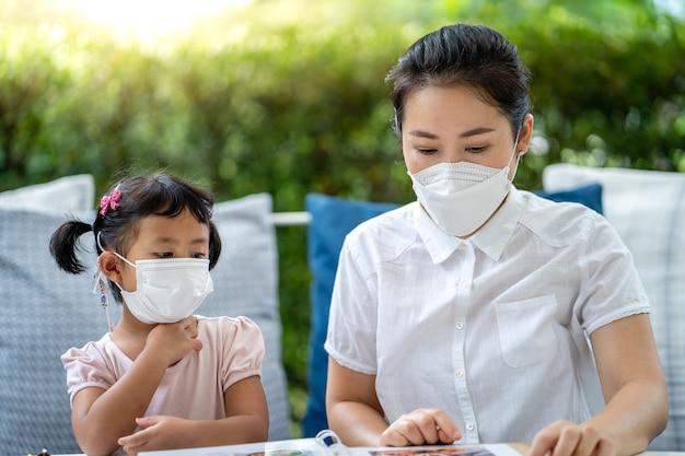 Moeder en dochter met beschermend gezichtsmasker zitten aan tafel en kijken naar menu's in restaurant