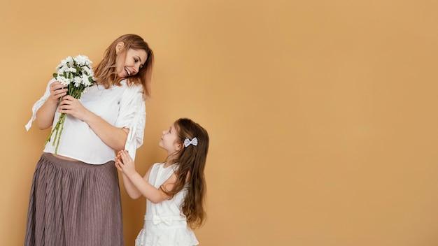 Moeder en dochter met boeket van lentebloemen en kopieer de ruimte