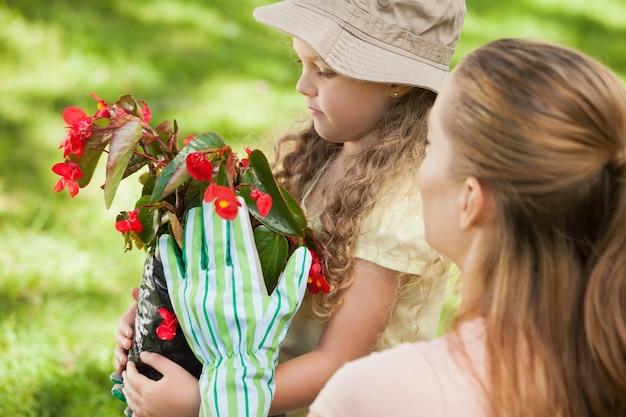 Moeder en dochter met een bloempot in het park