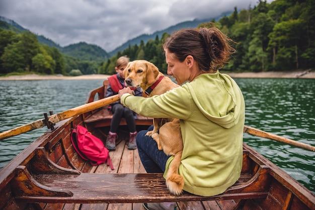 Moeder en dochter met een hond die een boot roeit