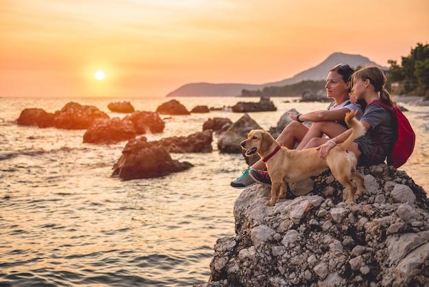 Moeder en dochter met een hond die langs de kust wandelt
