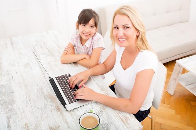 Moeder en dochter met een laptop thuis