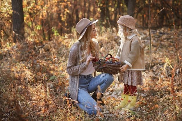 Moeder en dochter met een mand met bessen in het bos tijdens een wandeling in de herfst