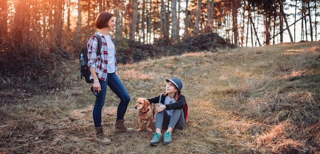 Moeder en dochter met hond in bos tijdens zonsondergang