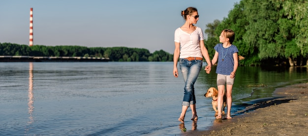 Moeder en dochter met hond wandelen door de rivier