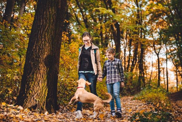 Moeder en dochter met hond wandelen