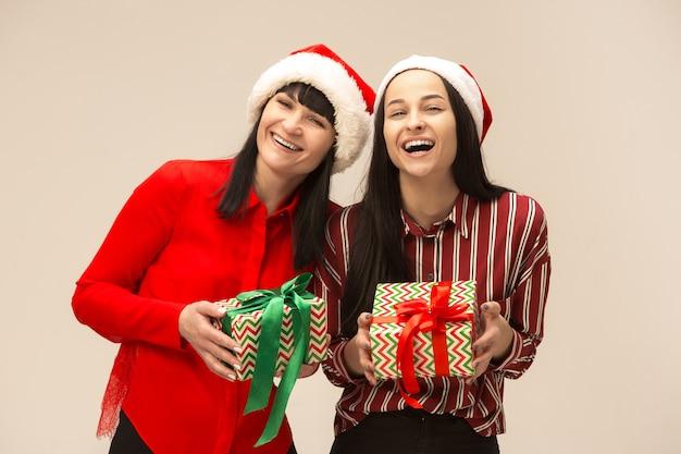 Moeder en dochter met kerstmuts en geschenkdoos