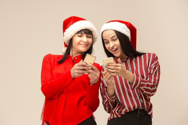 Moeder en dochter met kerstmuts met behulp van smartphones
