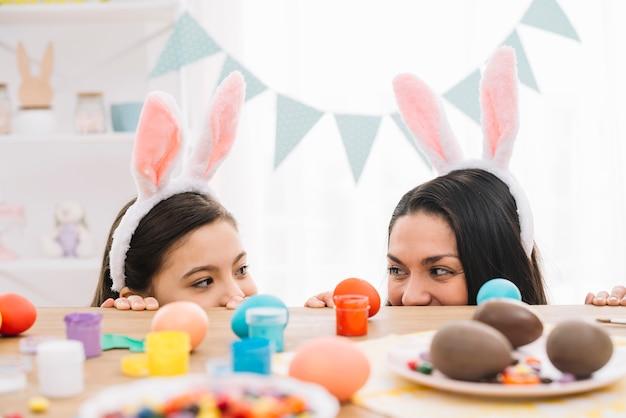 Moeder en dochter met konijnenoren gluren uit achter de tafel met smakelijke paaseieren