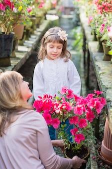 Moeder en dochter met planten, tuinieren in kas.