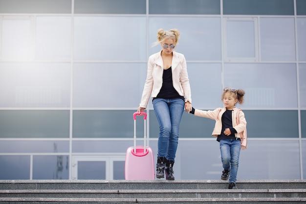 Moeder en dochter met roze bagage in roze jasje tegen de luchthaven.