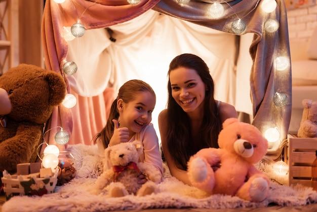 Moeder en dochter met teddyberen in huis.