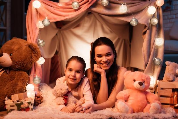 Moeder en dochter met teddyberen in kussenhuis.