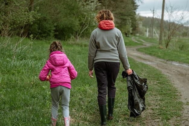 Moeder en dochter met vuilniszakken reinigen het milieu van afval.