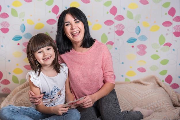 Moeder en dochter met wenskaart glimlachen
