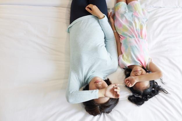 Moeder en dochter moe na het samen spelen, rustend op bed en ogen bedekken met armen, uitzicht vanaf de top